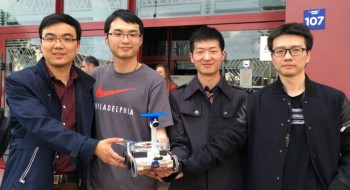 The team stand proudly with their robot. From L to R is